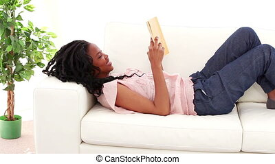 Cheerful woman reading a novel in her living room