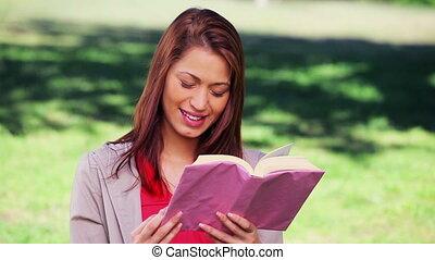 Cheerful woman reading an interesting novel