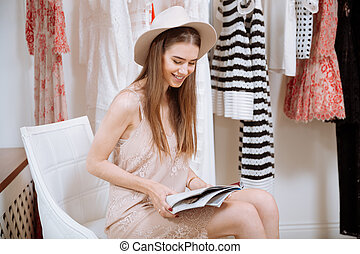 Cheerful woman reading magazine in clothes shop