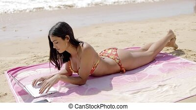 Cheerful woman relaxing on beach with laptop - Confident...