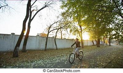Cheerful Woman rides a bike in autumn Park