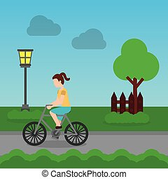 cheerful woman riding a bike on a park road