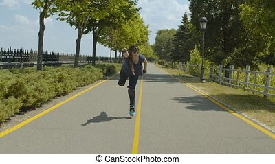 Playful female rollerblading along green park alley comically imitating superman riding one roller skate and stretching arm forward. Young woman with ponytail from afro-braids having fun during ride.