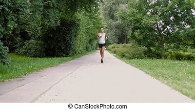Cheerful woman running in park