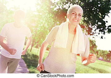 Cheerful woman running with her husband