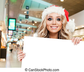 Cheerful woman Santa showing white empty paper signboard banner with copy space on shopping mall background. Christmas and New Year sale and offer concept