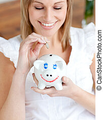 Cheerful woman saving money in a piggy-bank