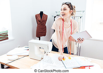 Cheerful woman seamstress with laptop at work