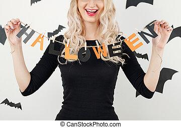 Cheerful woman showing Halloween garland
