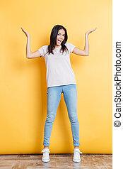 Cheerful woman shrugging shoulders