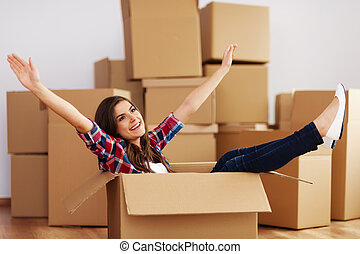 Cheerful woman sitting in a cardboard box