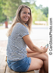 cheerful woman sitting in a park on a sunny day