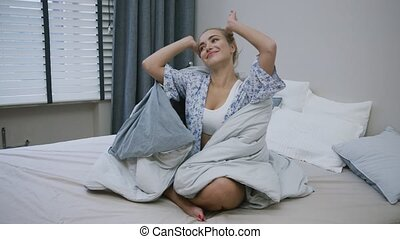 Cheerful woman sitting in bed