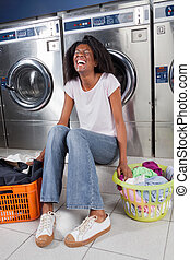 Cheerful Woman Sitting In Laundry