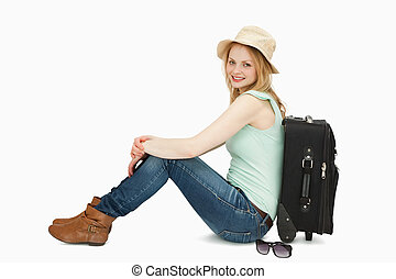 Cheerful woman sitting near a suitcase