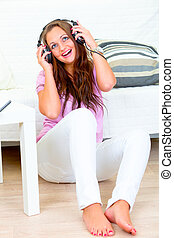 Cheerful woman sitting on floor and listening music in headphones at home