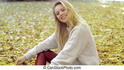 Cheerful woman sitting on ground - Beautiful cheerful woman...
