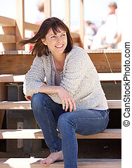 Cheerful woman sitting outdoors on steps