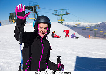 cheerful woman skiing on snowy mountain.