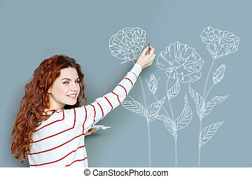 Cheerful woman smiling while drawing a flower