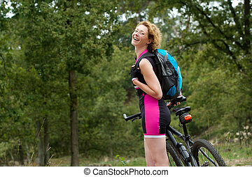 Cheerful woman smiling with bicycle outdoors