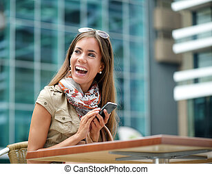 Cheerful woman smiling with mobile phone