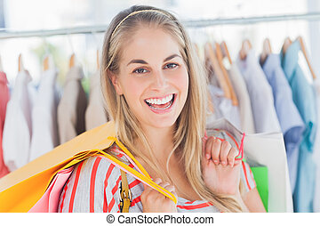 Cheerful woman standing in a clothing store and holding...