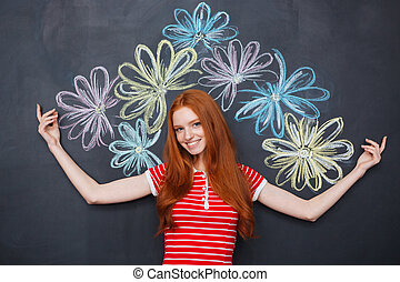 Cheerful woman standing over blackboard with drawn colorful...