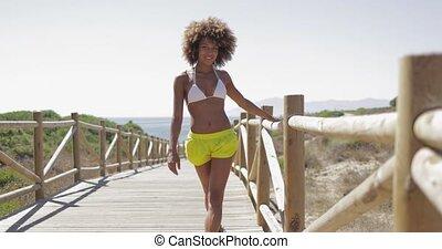 Cheerful woman strolling on coastline