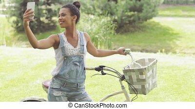 Cheerful woman taking selfie in park