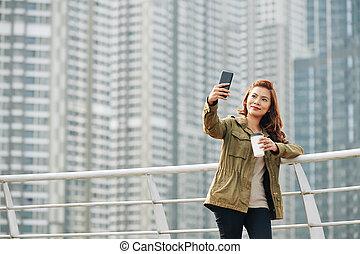 Cheerful woman taking selfie