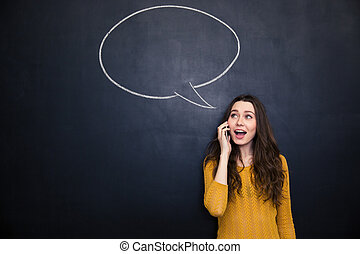 Cheerful woman talking on cellphone over blackboard with  speech bubble
