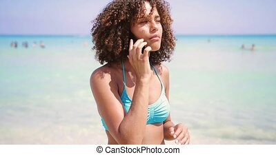Cheerful woman talking on phone at seaside
