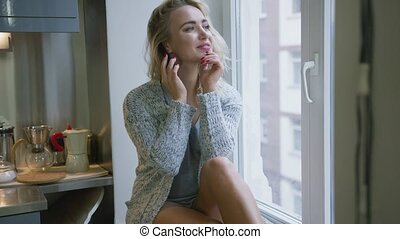 Cheerful woman talking on phone near window