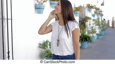 Cheerful woman talking phone at street