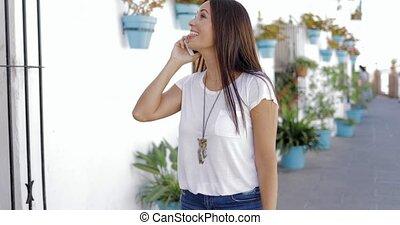 Cheerful woman talking phone at street