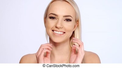 Cheerful Woman Touching her Face Against White