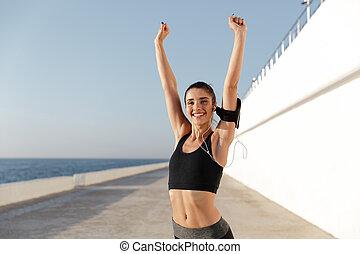 Cheerful woman training near sea