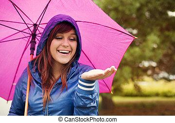 Cheerful woman under pink umbrella checking for rain