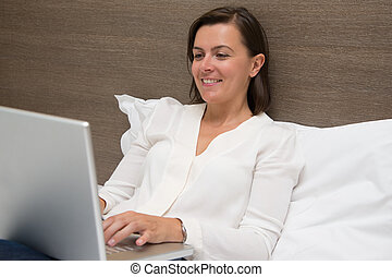 Cheerful woman using her laptop in the bedroom