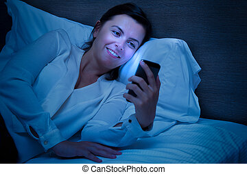 Cheerful woman using her smart-phone in the bedroom