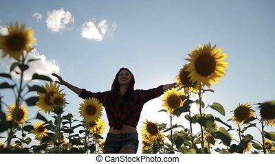 Cheerful woman walking in field of sunflowers