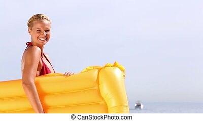 Cheerful woman waving hello and holding lilo at the beach