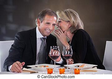 Cheerful Woman Whispering Something In Man's Ear In A Elegant Restaurant