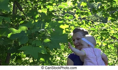 cheerful woman with baby daughter have fun between tulip tree branches. 4K