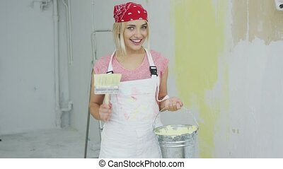 Cheerful woman with brush and paint bucket
