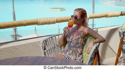 Cheerful woman with cocktail resting on hotel balcony - Glad...