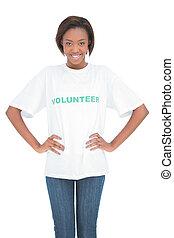 Cheerful woman with hands on hips wearing volunteer tshirt ...