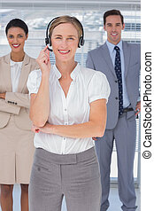 Cheerful woman with headset standing in front of smiling business people