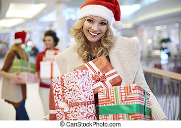 Cheerful woman with heap of christmas gifts